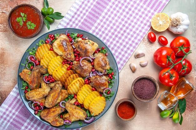 Top vista ravvicinata pollo ali di pollo patate limone olio aglio pomodori spezie