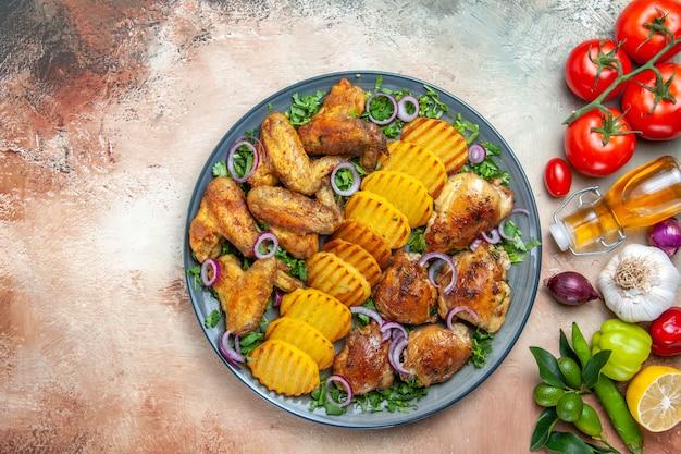 Вид сверху крупным планом курица куриные крылышки картофель лук зелень лимонное масло лук сладкий перец помидоры