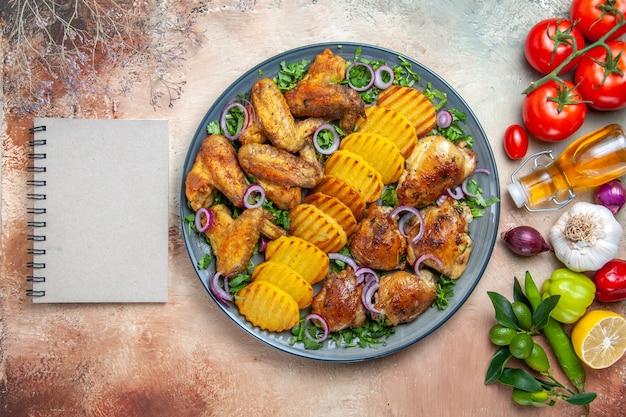 Вид сверху крупным планом курица куриные крылышки картофель лук зелень овощи белый блокнот