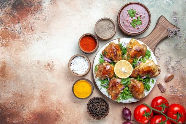 Top vista ravvicinata pollo pollo con spezie limone pomodori salsa di spezie