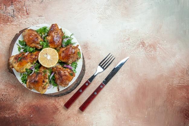 Top vista ravvicinata pollo pollo con erbe aromatiche e cipolla sul lavash sulla tavola forchetta coltello