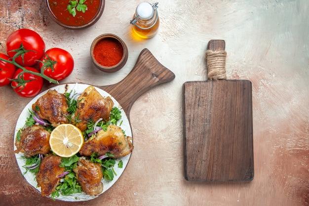 Top vista ravvicinata pollo pollo con erbe salsa di pomodori spezie bottiglia di olio la tavola di legno