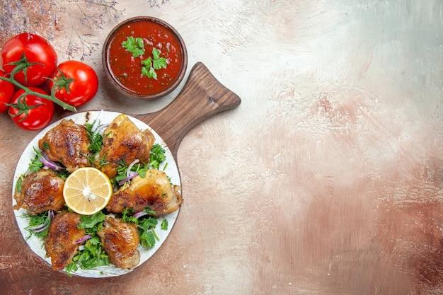 Вид сверху крупным планом курица, курица с лимонными травами на доске, соус, помидоры с цветоножками