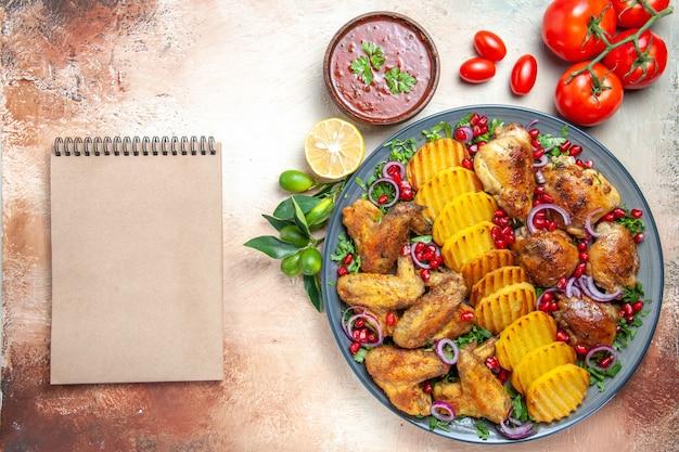 Top vista ravvicinata pollo salsa di pollo con taccuino di crema di pomodori melograno patate Foto Gratuite