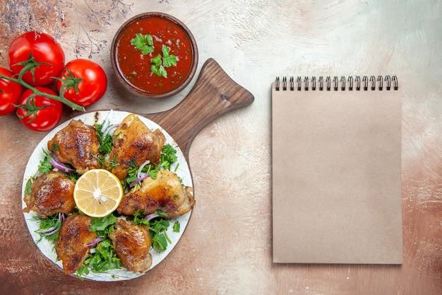Top vista ravvicinata pollo salsa di pomodori pollo con erbe di limone sul taccuino di crema di bordo