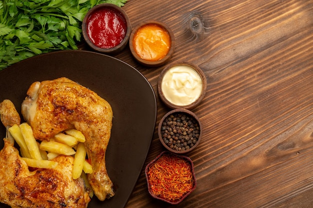 Top close-up view chicken and spices appetizing chicken legs french fries next to the herbs bowls of different sauces and spices