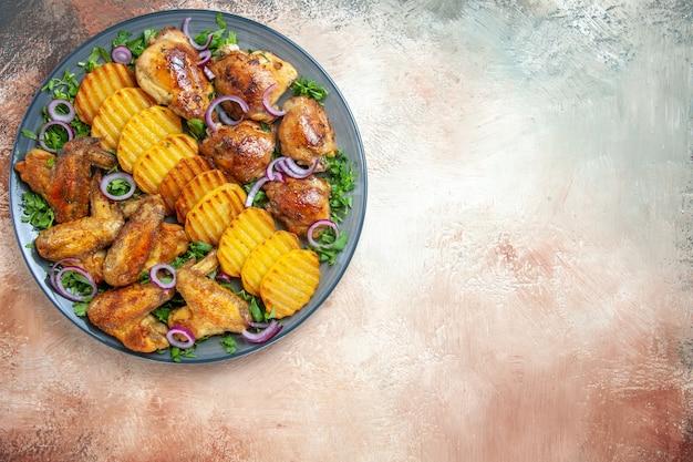 Вид сверху крупным планом куриные крылышки куриные крылышки картофель лук зелень на столе