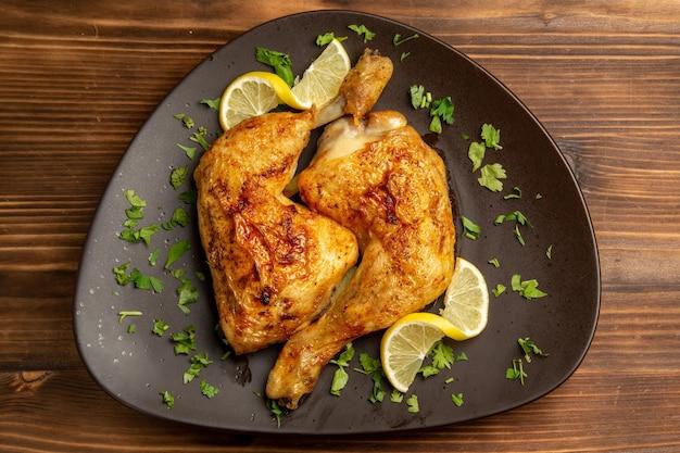 테이블 중앙에 있는 갈색 접시에 허브와 레몬을 넣은 허브 치킨 다리가 있는 클로즈업 보기 치킨