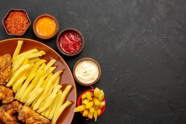 Вид сверху крупным планом курица и картофель, куриные крылышки, картофель фри и лимон, три миски с разными видами соусов и специй на темном столе
