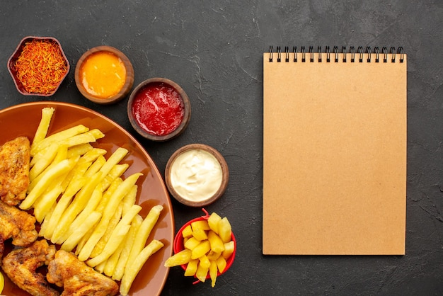 Top close-up view chiken and potatoes chicken wings french fries and lemon three bowls of different types of sauces and spices next to the cream notebook on the dark table