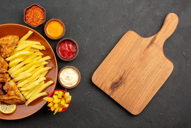 Top close-up view chiken and potatoes chicken wings french fries and lemon three bowls of different types of sauces and spices next to the wooden cutting board on the dark table