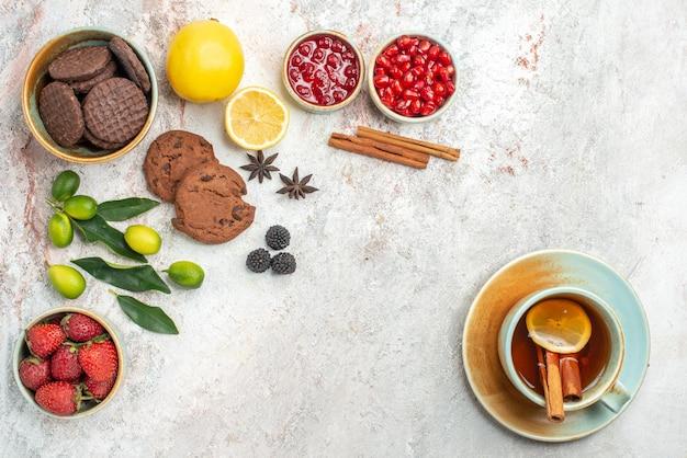 상단 클로즈업 보기 초콜릿 쿠키 초콜릿 쿠키 레몬과 계피 스틱이 든 차 한 잔은 테이블에 베리 감귤류 과일 그릇을 얹습니다.