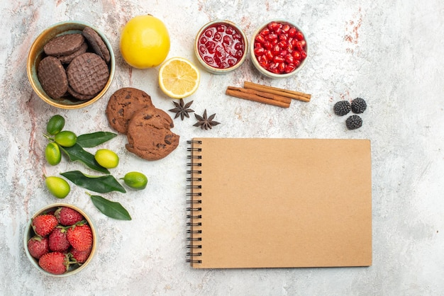 上部のクローズアップビューチョコレートクッキークリームノートブックチョコレートクッキーベリーのボウル柑橘系の果物シナモンスティックテーブルに