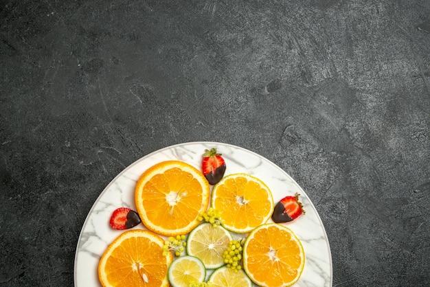 어두운 배경에 있는 접시에 얇게 썬 레몬 오렌지와 초콜릿으로 덮인 딸기를 맛있게 먹는 초콜릿 덮인 딸기
