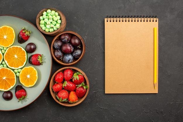 연필과 크림 공책 옆에 초콜릿으로 덮인 딸기 초콜릿으로 덮인 딸기 녹색 사탕 다진 오렌지와 다양한 과일 딸기와 과자 그릇