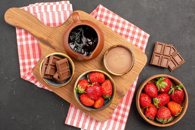 체크 무늬 식탁보에 있는 주방 보드에 있는 초콜릿 크림 초콜릿 크림과 딸기, 테이블 중앙에 있는 딸기와 초콜릿 접시