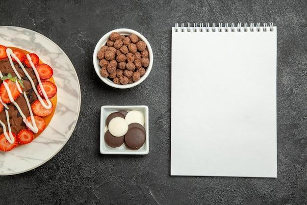 Vista ravvicinata dall'alto crema al cioccolato fragole ciotole di appetitosa torta al cioccolato e nocciole con frutti di bosco accanto al quaderno bianco