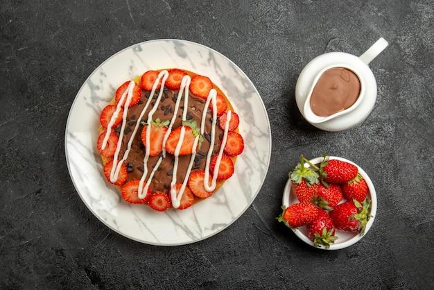 Вид сверху крупным планом шоколадный крем клубника миски клубники и шоколадный крем торт с клубникой и шоколадом