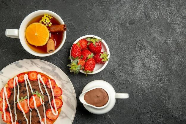 Vista ravvicinata dall'alto torta di fragole crema al cioccolato con fragole e cioccolato e una tazza di tè accanto alle ciotole di fragole e crema al cioccolato sul lato sinistro del tavolo scuro