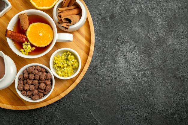 Vista ravvicinata dall'alto cioccolato al limone ciotole di crema al cioccolato nocciole una tazza di tè con bastoncini di cinabro e limone sul lato sinistro del tavolo