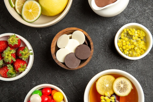Vista ravvicinata dall'alto ciotole di cioccolato e fragole di erbe al cioccolato e fragole accanto alla tazza di tisana sul tavolo scuro