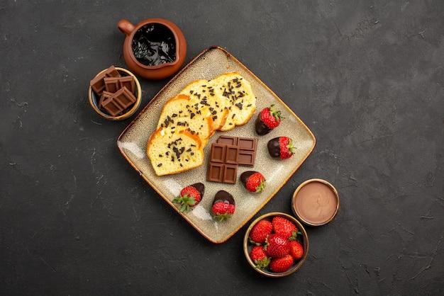 상위 클로즈업 보기 초콜릿 딸기 케이크 딸기 초콜릿 크림과 초콜릿은 어두운 탁자 중앙에 있는 식욕을 돋우는 케이크와 딸기를 그릇에 담고 있습니다.