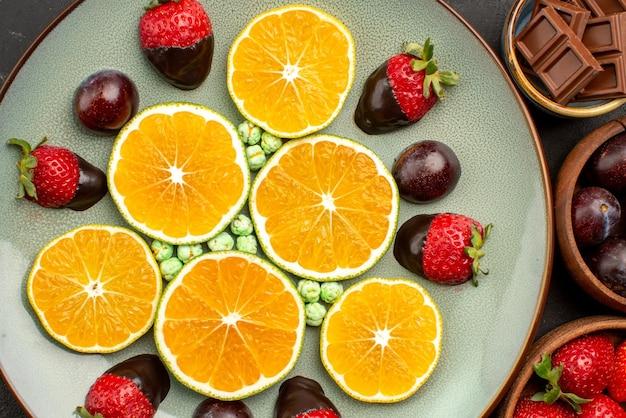Вид сверху крупным планом нарезанный апельсин и шоколад белая тарелка нарезанного апельсинового шоколада и конфет рядом с мисками шоколада и ягод на темном фоне