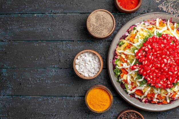 Vista ravvicinata dall'alto piatto di natale con melograni un appetitoso piatto di natale con semi di melograno accanto ai rami degli alberi e cinque ciotole di spezie colorate sul tavolo