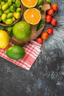 上部のクローズアップビュー柑橘系の果物リンゴチェリーテーブルクロスの柑橘系の果物ボード上の