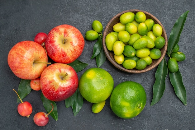 Top vista ravvicinata di agrumi ciotola di agrumi con foglie mele ciliegie mandarini