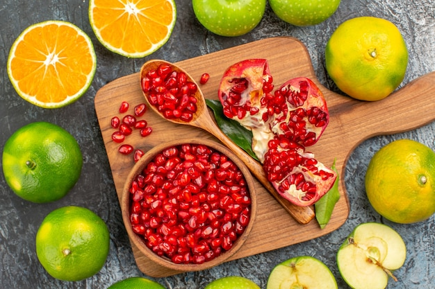 Top close-up view citrus fruits citrus fruits around the board with pomegranate seeds