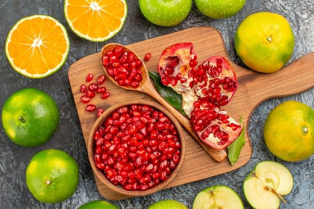 Top vista ravvicinata agrumi agrumi intorno al tabellone con semi di melograno