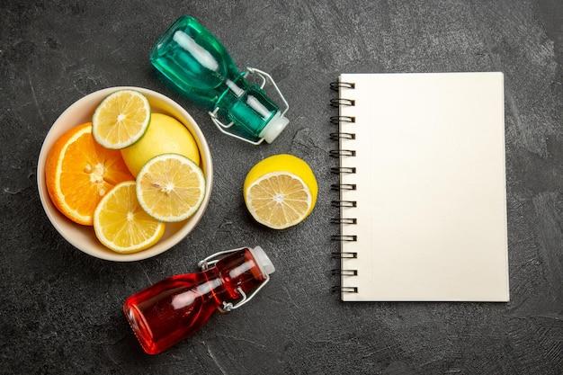 Цитрусовые фрукты крупным планом цитрусовые в миске рядом с белым блокнотом и двумя бутылками на темном столе