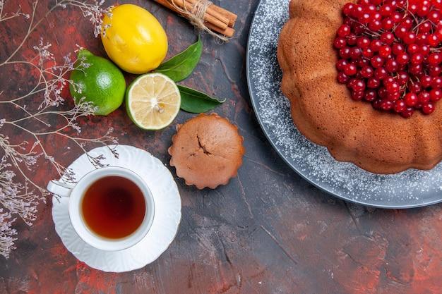 Vista ravvicinata dall'alto torta di cupcake agli agrumi con bacche di cannella una tazza di rami di lime di tè