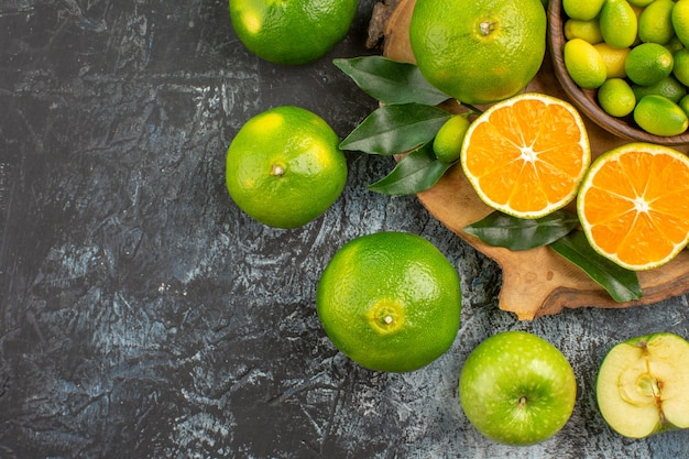 Top close-up view citrus fruits oranges mandarins green apples on the cutting board