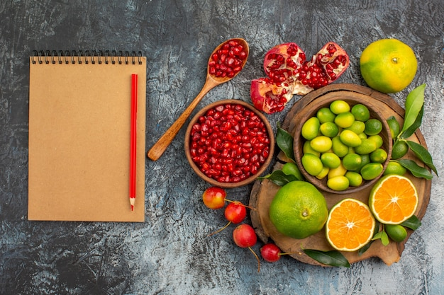 Top close-up view citrus fruits pomegranate seeds spoon citrus fruits on the board notebook pencil