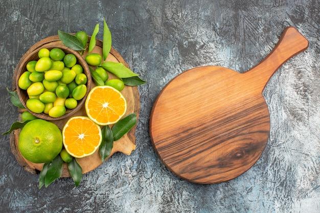 Вид сверху крупным планом цитрусовые фрукты аппетитные цитрусовые с листьями на разделочной доске