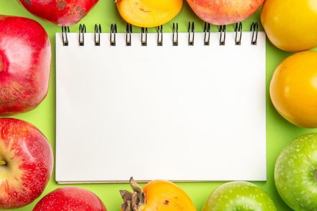 緑のテーブルの上の白いノートの横にあるカラフルな果物カラフルな果物の上部のクローズアップビュー