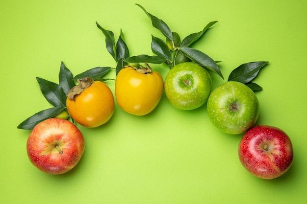Top close-up view colorful fruits green and red apples persimmons with leaves
