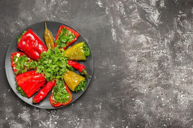 Top vista ravvicinata peperoni colorati pepe colorato con erbe sulla banda nera