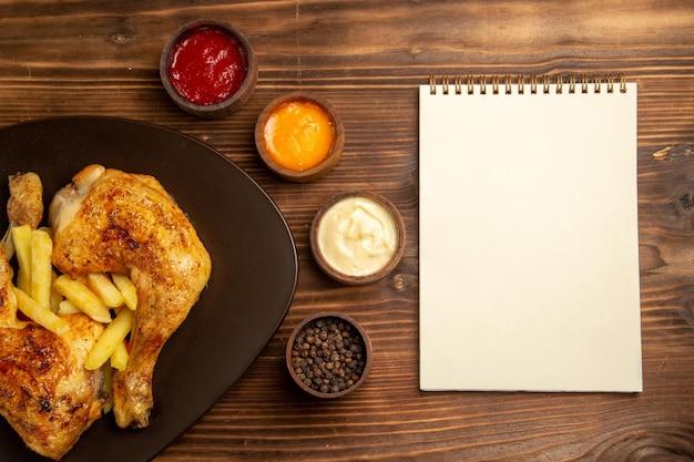 Vista ravvicinata dall'alto salse colorate quaderno bianco ciotole di salse colorate e pepe nero accanto al piatto di pollo e patatine fritte