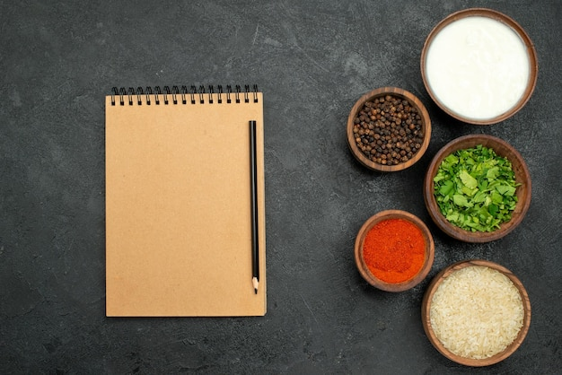 Top close-up view colorful spices bowls of colorful spices herbs black pepper sour cream and rice on the right side of grey table next to cream notebook and pencil
