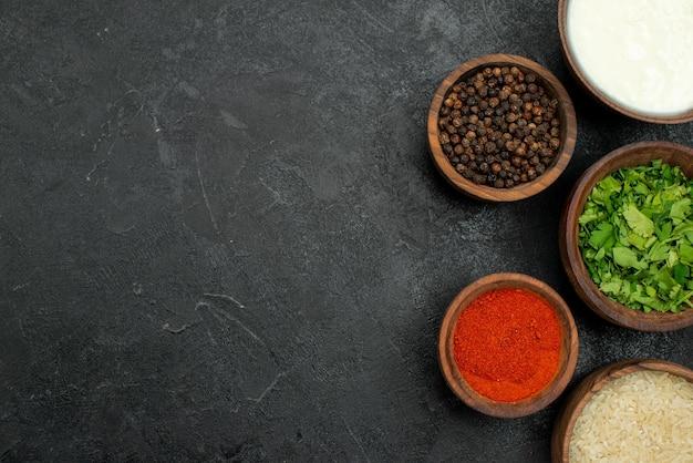 Вид сверху крупным планом красочные чаши для специй с красочными специями, черный перец, травы, сметана и рис на правой стороне стола