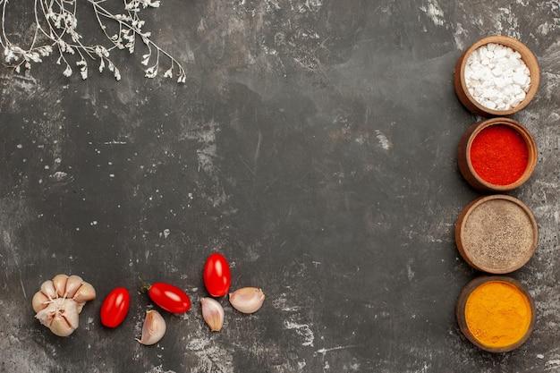 Vista ravvicinata dall'alto spezie colorate quattro ciotole di spezie colorate aglio e pomodori accanto ai rami degli alberi sul tavolo nero