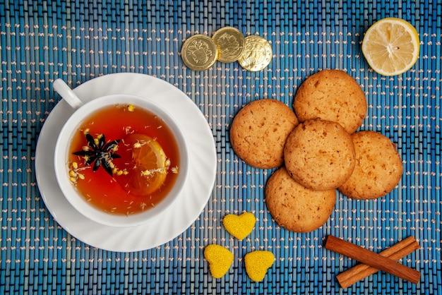 Вид сверху крупным планом печенье и чашка чая вкусное печенье палочки корицы лимонные конфеты и чашка травяного чая с лимоном на скатерти