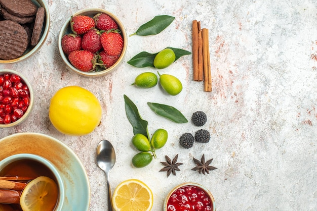 Top close-up view cookies and berries cinnamon the appetizing cookies strawberries lemon spoon a cup of tea citrus fruits on the table
