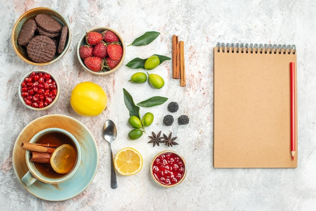 Top close-up view cookies and berries cream notebook and red pencil next to the cinnamon the appetizing cookies strawberries lemon spoon a cup of tea citrus fruits on the table