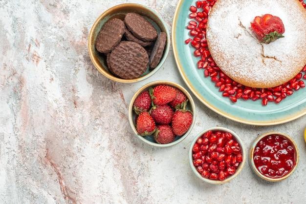 テーブルの上のさまざまなベリークッキーのイチゴとザクロのボウルの上部のクローズアップビュークッキーケーキ