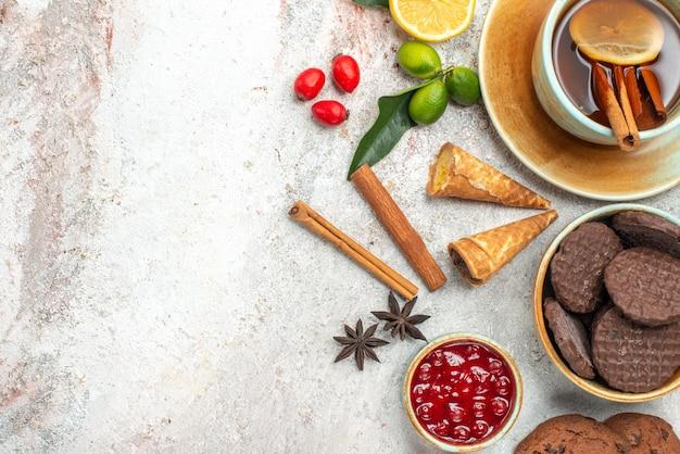 Vista ravvicinata dall'alto biscotti una tazza di tè con limone bastoncino di cannella marmellata di agrumi anice stellato