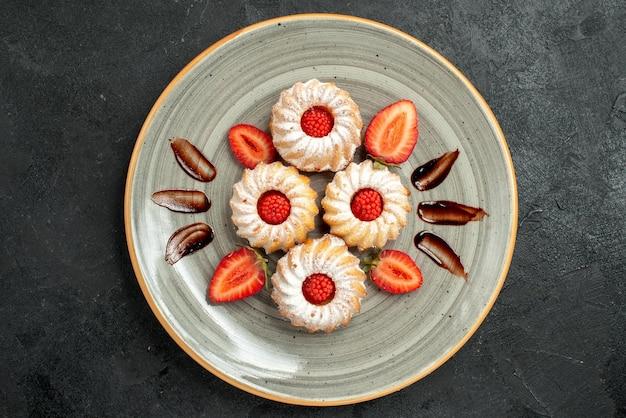 테이블 중앙에 있는 흰색 접시에 초콜릿과 딸기를 곁들인 식욕을 돋우는 딸기 쿠키가 있는 클로즈업 보기 쿠키
